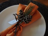 table setting with orange napkins and pinecones