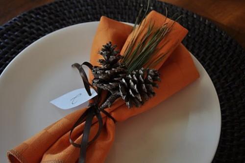 table setting with orange napkins and pinecones (via themotherhuddle)