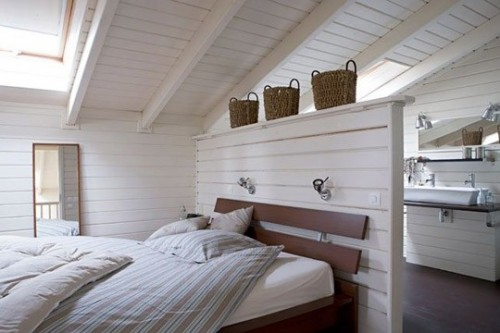 If you have an attic guest bedroom and an attic bathroom near by you can simply separate them with a wall right behind a bed. It would act as a headboard too.