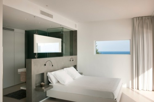 Hotel-like glass and concrete divider for a bathroom and a bedroom.