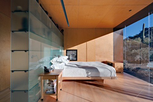 Glass shelving system also works well for the space behind a bed.