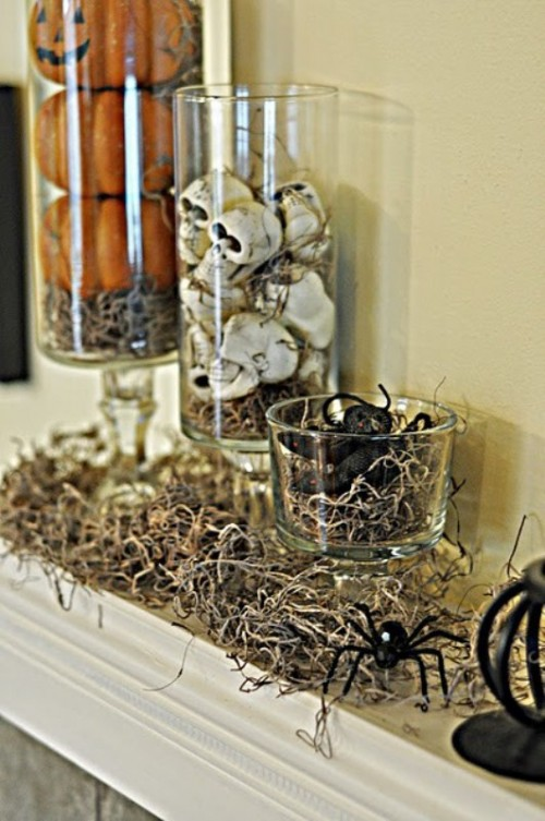 a Halloween mantel with hay, spiders in a glass jar, skulls and orange pumpkins is a timeless Halloween decor idea