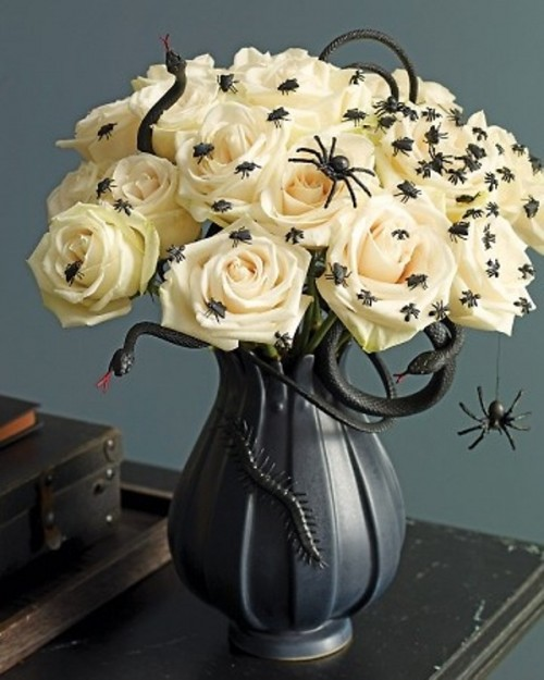 a beautiful and scary Halloween centerpiece of a black vase with white roses and spiders plus a black snake