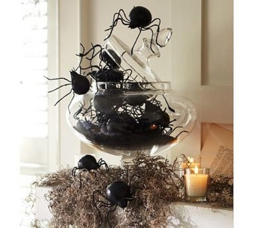 a scary Halloween decoration or centerpiece of hay, a glass jar with large spiders and candles is fantastic