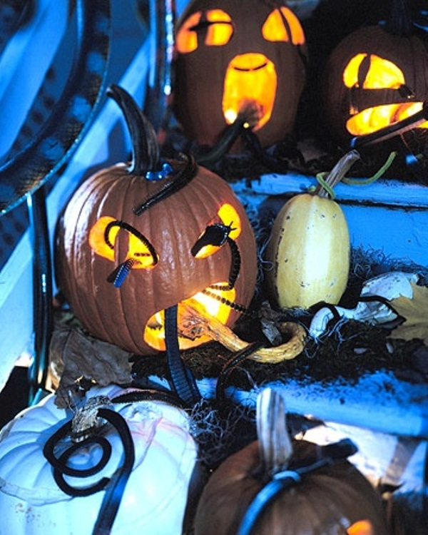 scary carved pumpkins with snakes, spiders and lights are very spooky decorations for Halloween