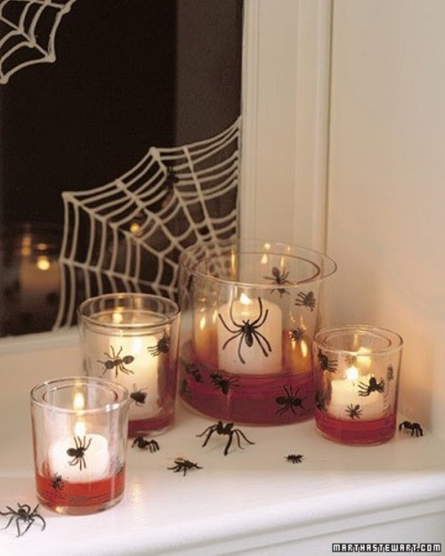 lots of candleholders of glass and mini spiders are nice for Halloween decor and a spiderweb on the window