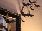 black paper bats decorating the mirror and the wall are amazing for Halloween decorating and won't cost much effort