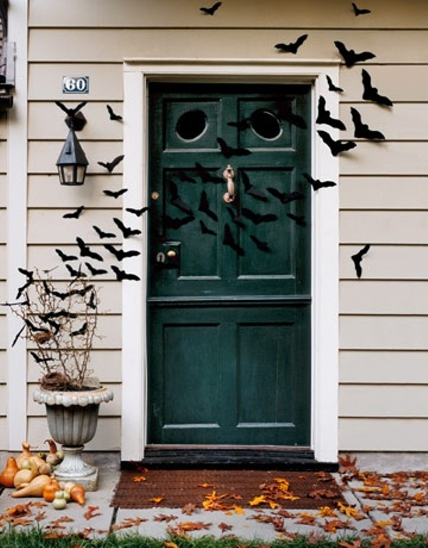outdoor Halloween decor with lots of paper bats attached to the walls and door, fall eaves and stacked pumpkins