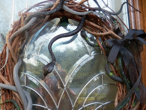 a vine wreath with snakes and a black bow is a refined and chic Halloween decor idea