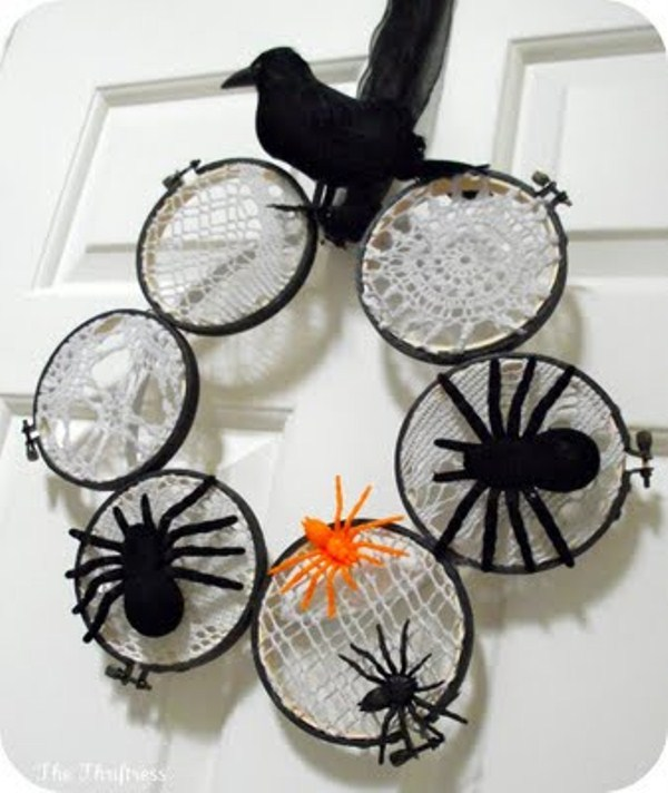 a creative Halloween wreath of embroidery hoops with macrame and lace, spiders of various colors and a blackbird on top