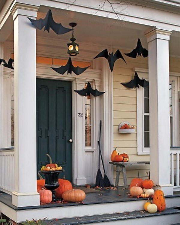 oversized paper bats hanging over the porch and stackes of pumpkins and brooms make the space look very Halloween inspired