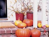 bright natural pumpkins and blooming branches with leaves in buckets for a natural fall Thanksgiving porch