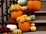natural pumpkins stacked and used as vases for bright fall blooms will make your front porch cozy and fall-like