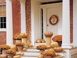 a rust, tan and gold fall porch decor with pumpkins and potted blooms is a very soft and beautiful option