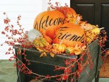 a cart with colorful pumpkins and letters, faux leaves and branches with berries will bring a rustic fall feel to the porch