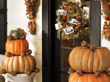 cozy traditional Thanksgiving porch decorating with stacked pumpkins in natural colors, fall leaves and cool bundles and a wreath with leaves, acorns and wheat