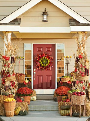 a bold rustic Thanksgiving porch styled with bright blooms in planters, corn husks, bold apples in woodne baskets, gourds and pumpkins on it