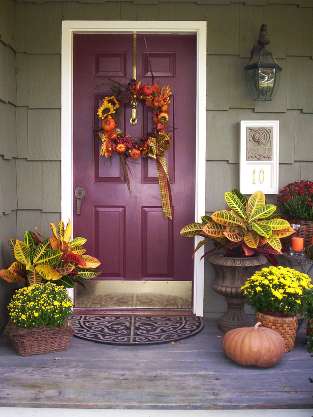 bright yellow flowers in baskets, pumpkins, candles and a cool faux pumpkin and bloom wreath
