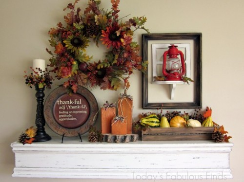 a decorative plate, a candle, a wooden box with faux veggies and fruit, a lantern, a faux leaf wreath and wooden pumpkins