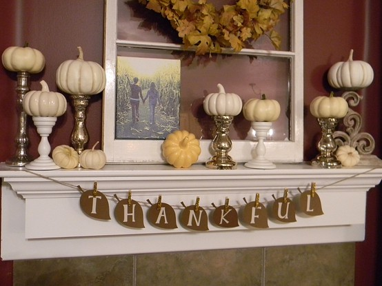 a leaf garland, white pumpkins on stands, a family pic and a fall leaf wreath over the mantel
