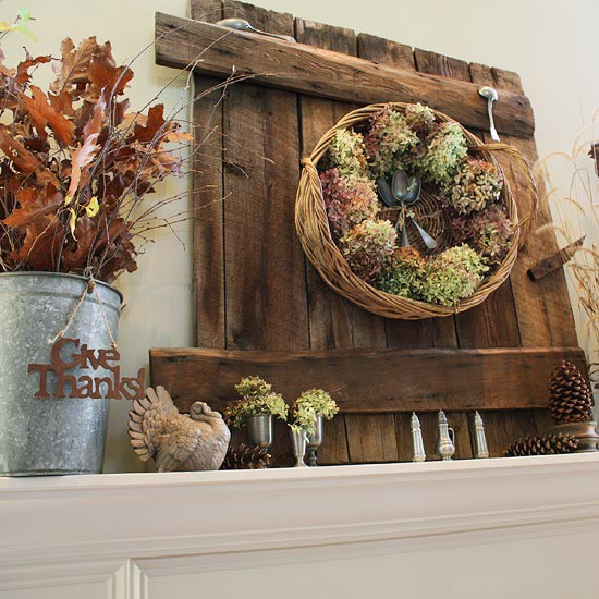 a Thanksgiving mantel with a wooden board, a basket with hydrangeas and spoons, pinecones, fall leaves and a turkey figurine