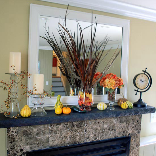 candles, faux pumpkins and gourds, bright fall leaves, feathers and faux leaves in a vase for a Thanksgiving mantel