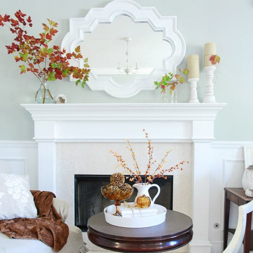 neutral candles in candleholders and bright fall leaves on branches for decorating your mantel for Thanksgiving in modern style