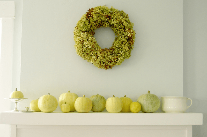 white, green and yellow pumpkins and a grene hydrangea wreath over the mantel are stylish Thanksgiving decor