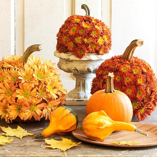 bright pumpkins and gourds, pumpkins covered with rust and orange blooms is a stylish Thanksgiving centerpiece