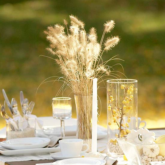 a neutral fall or Thanksgiving centerpiece of dried wheat, berries in a stained glass and a candle in a candleholder