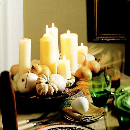 a harvest centerpiece of a wooden bowl with pumpkins, pears, wheat and candles is easy to compose and very rustic