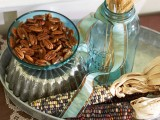 a fall or Thanksgiving centerpiece of wheat, corn cobs and pecans in a bowl is a stylish and all-natural idea