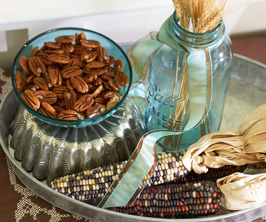 a fall or Thanksgiving centerpiece of wheat, corn cobs and pecans in a bowl is a stylish and all natural idea