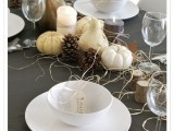 a Thanksgiving centerpiece of gourds, pumpkins, pinecones, candles, hay and tree stumps is very natural and rustic