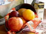 a metal shovel with apples, pears and prunes plus a bright napkin is a stylish fall or Thanksgiving centerpiece