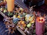 a wooden bowl with acorns, nuts, pinecones, gourds, pumpkins and candles is a cozy rustic idea of a centerpiece