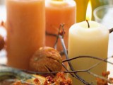 a modern rustic centerpiece of branches, blooms, pumpkins and natural-colored candles for fall and Thanksgiving