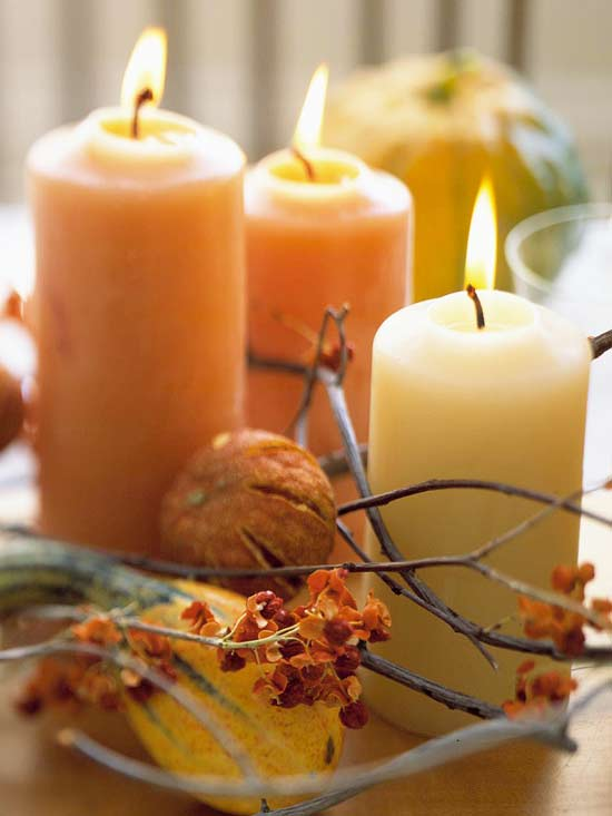 a modern rustic centerpiece of branches, blooms, pumpkins and natural colored candles for fall and Thanksgiving
