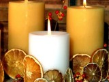 a natural fall centerpiece of tan and white candles covered with dried citrus and berries is a nice idea that you can easily make