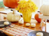 white and bright pumpkins and colored potted blooms create a simple rustic centerpiece for fall