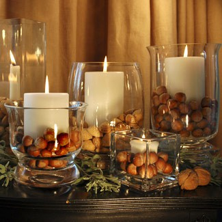 glass candleholders with candles and nuts around is a fast to make and easy fall and Thanksgiving centerpiece