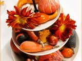 a tiered Thanksgiving centerpiece of faux gourds, pumpkisn and blooms will last really long and can be used year after year