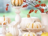 a refined and easy fall centerpiece of neutral pumpkins on stands and branches with berries in a vase