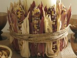 a large candle covered with corn cobs and husks is a beautiful rustic centerpiece for Thanksgiving