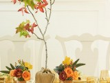 a fall centerpiece of bright blooms in baskets and a mini tree in burlap is a very creative idea