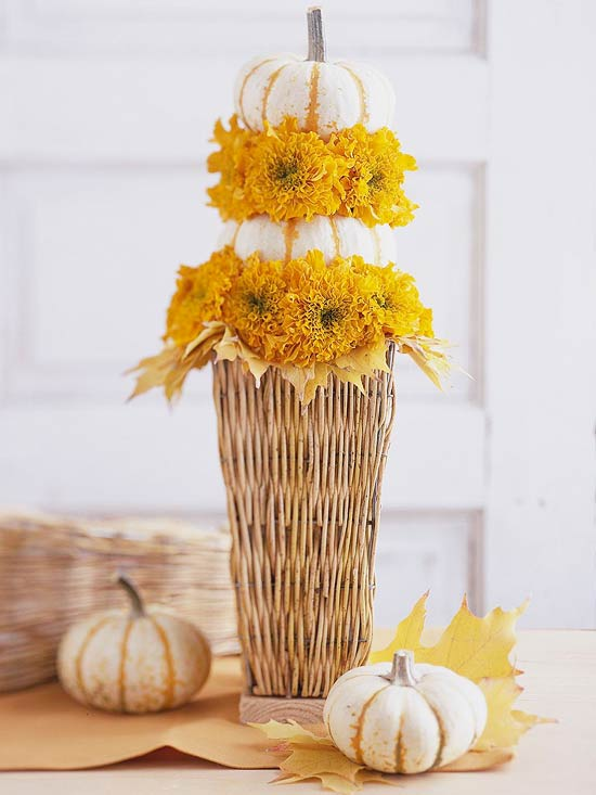 a tall basket with bright blooms and pumpkins, wiht leaves and pumpkins around is a cool fall centerpiece