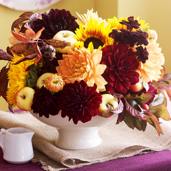 a bold and bright Thanksgiving centerpiece of a bowl with fruits and bright blooms and fall leaves is very cool