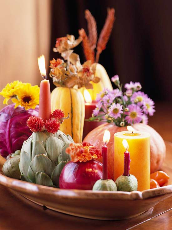 a porcelain bowl with pumpkins, cabbages, artichokes, pears, bright blooms and bold candles is a creative harvest centerpiece