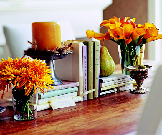 a simple Thanksgiving centerpiece of bright blooms in glass vases and a rust colored candle in a candleholder