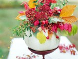a wood stand with a pale pumpkin, bright leaves, berries and bold blooms is a lovely and chic fall centerpiece to rock